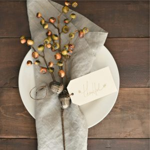 sprigs of acorns wrapped in natural colored linen napkin on white plate