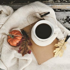small pumpkin with coffee and leaves on unknown book all sitting on cream blanket
