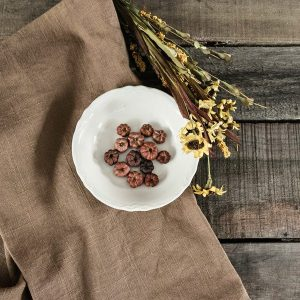 mini dried pumpkins in white bowl on brown linen napkin with dried flowers next to it